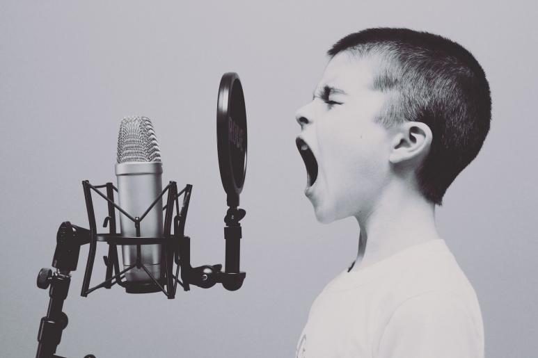 Ein Kind singt vor einem Studiomikrofon